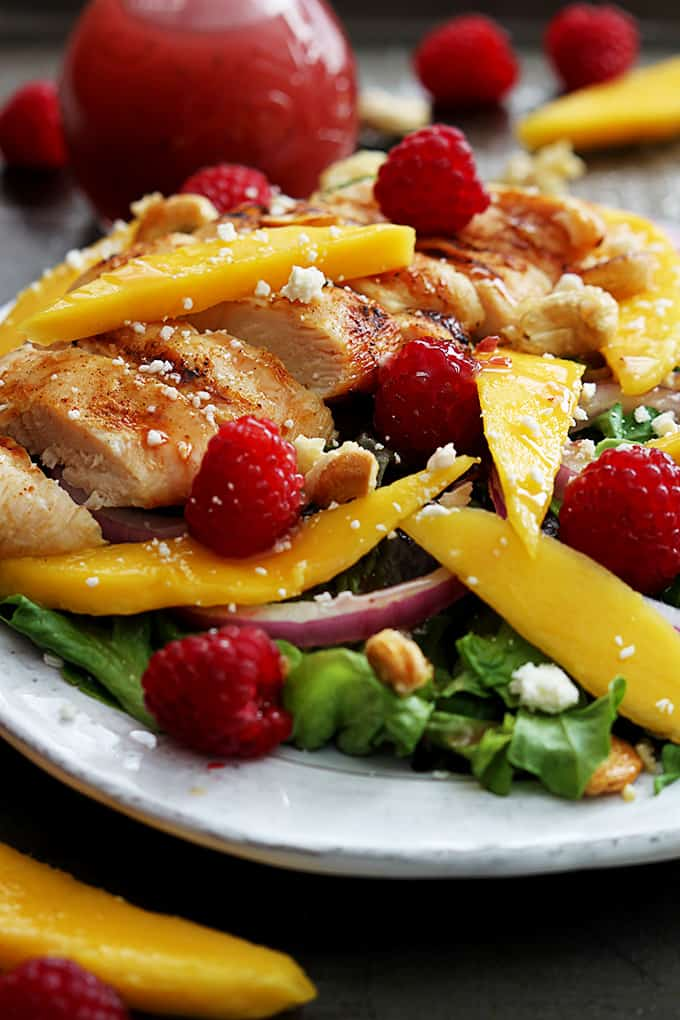 raspberry mango chicken cashew salad on a plate surrounded by more fruit.