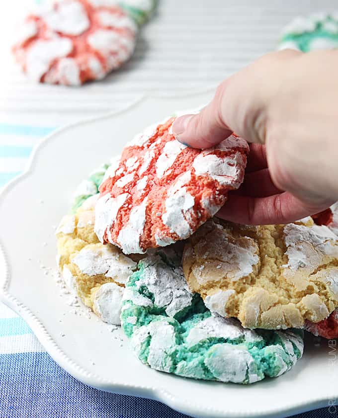 a hand taking a red white + blue crinkle cookie from a plate of cookies with more cookies faded in the background.