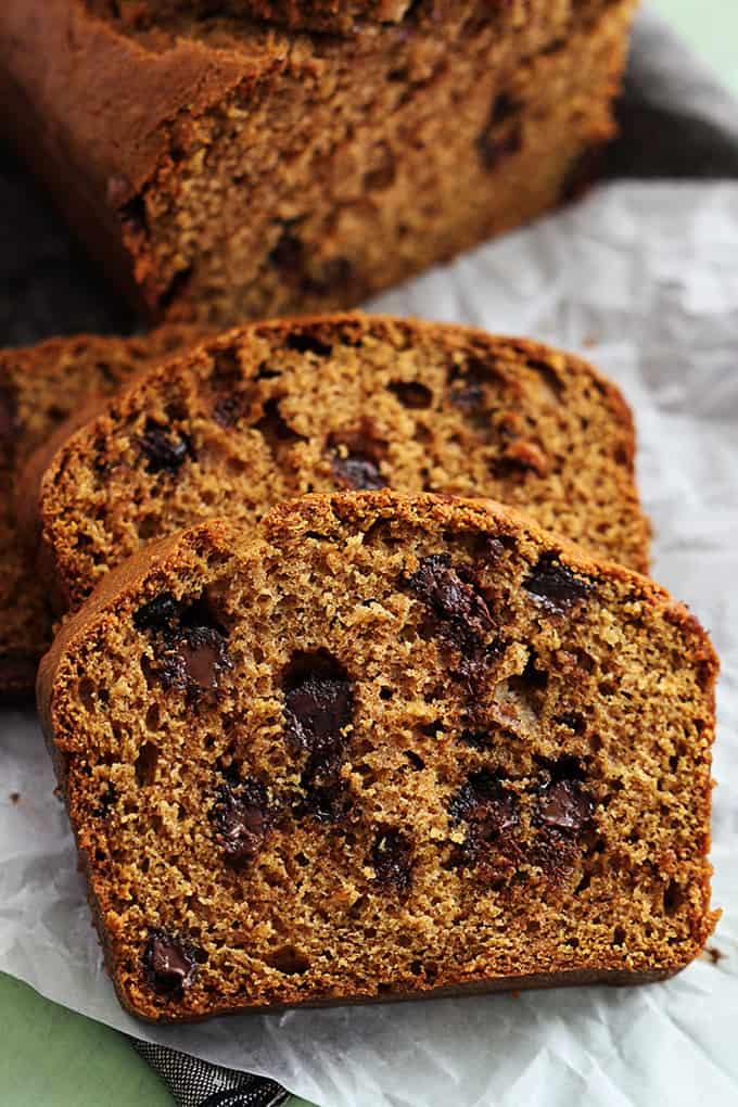 slices of browned butter chocolate chip pumpkin bread with the rest of the loaf in the background.