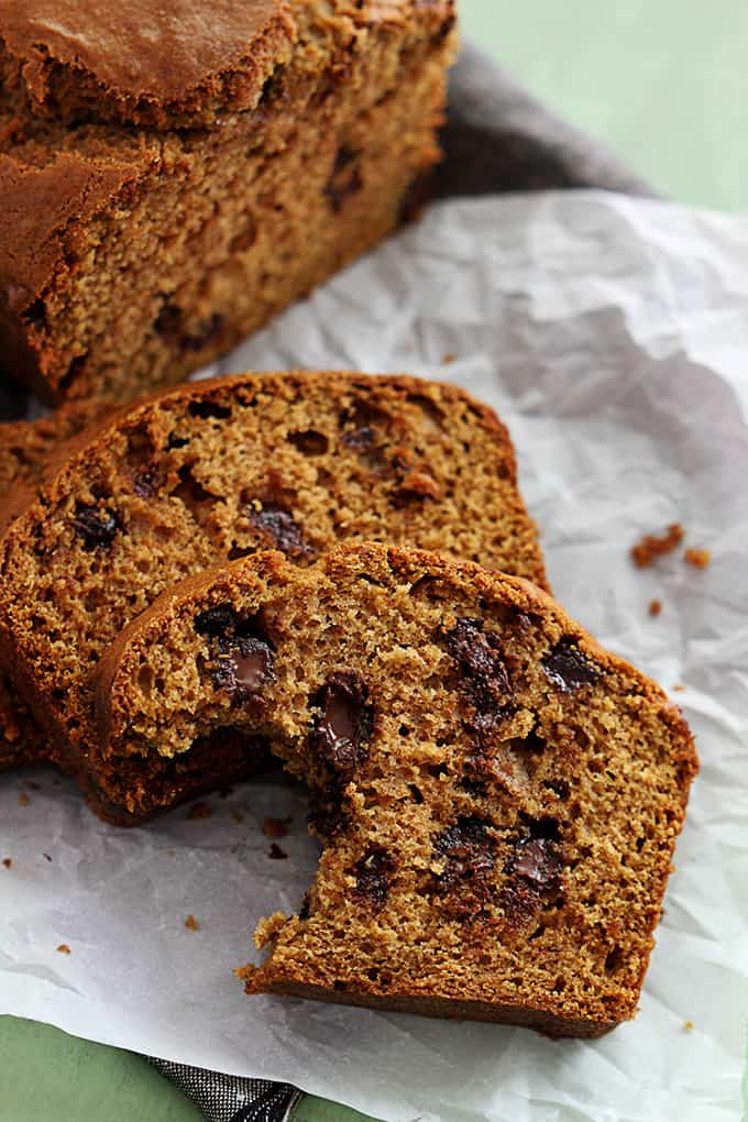 slices of browned butter chocolate chip pumpkin bread with the front slice missing bite and the rest of the loaf in the background.