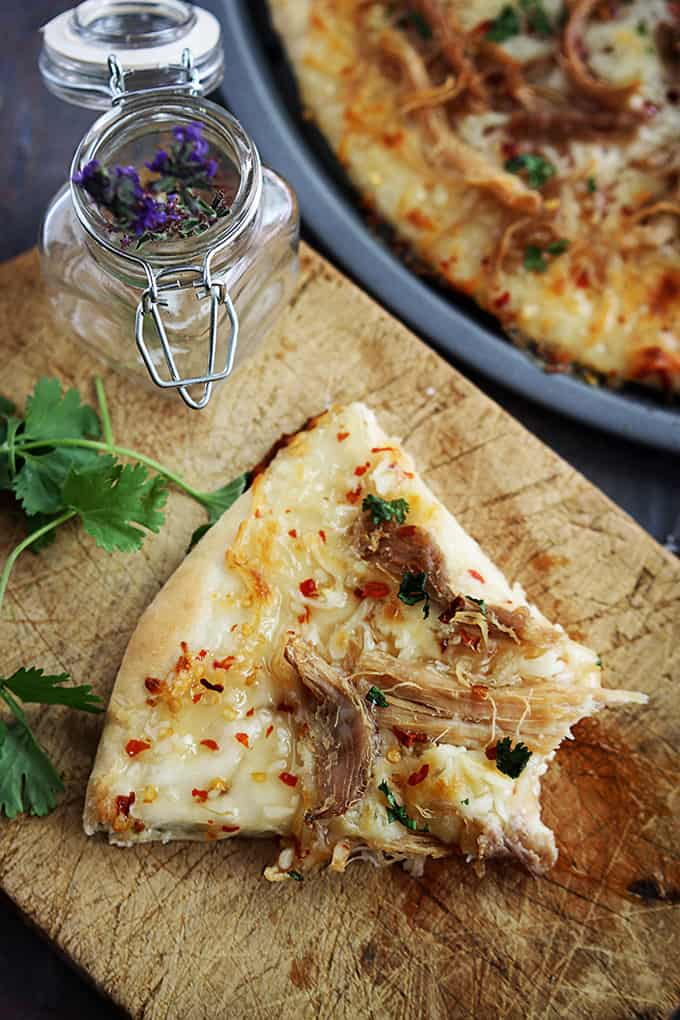 a slice of Thai sweet chili pork pizza with a bite missing on a wooden cutting board with a jar of spices next to it and the rest of the pizza on the side.