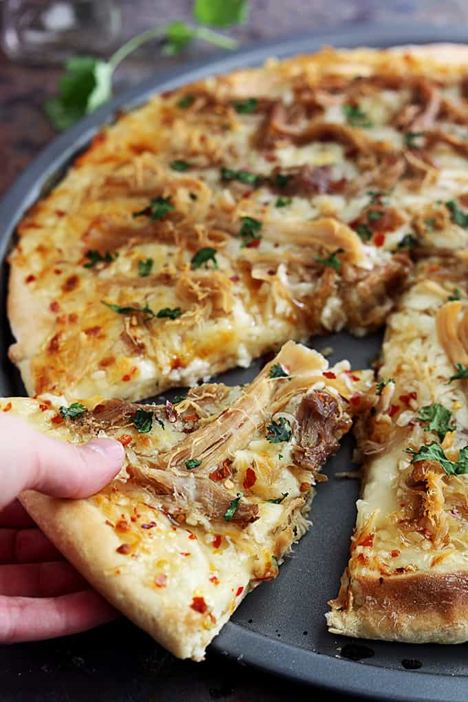 a hand taking a slice of Thai sweet chili pork pizza.