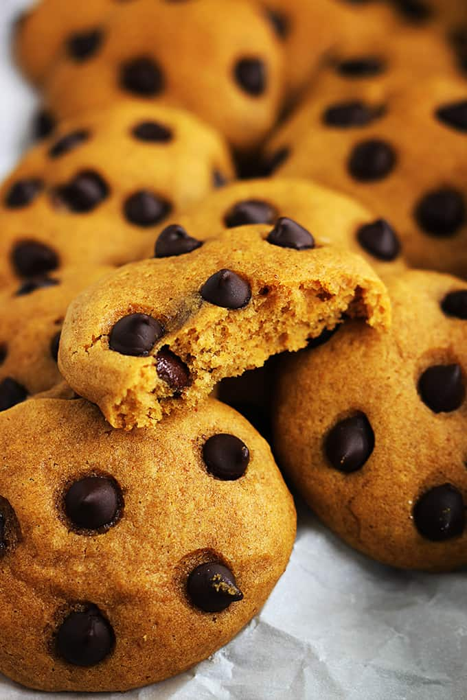 close up of pumpkin chocolate chip cookies with half of a cookie on top of the rest.