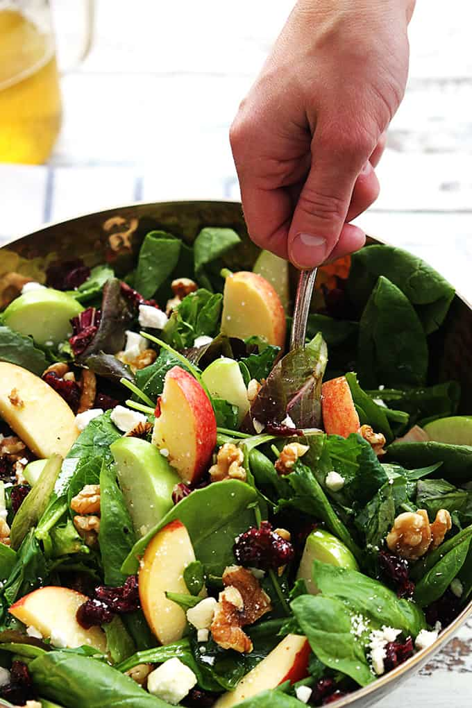 a hand scooping some apple cranberry walnut salad from a bowl.