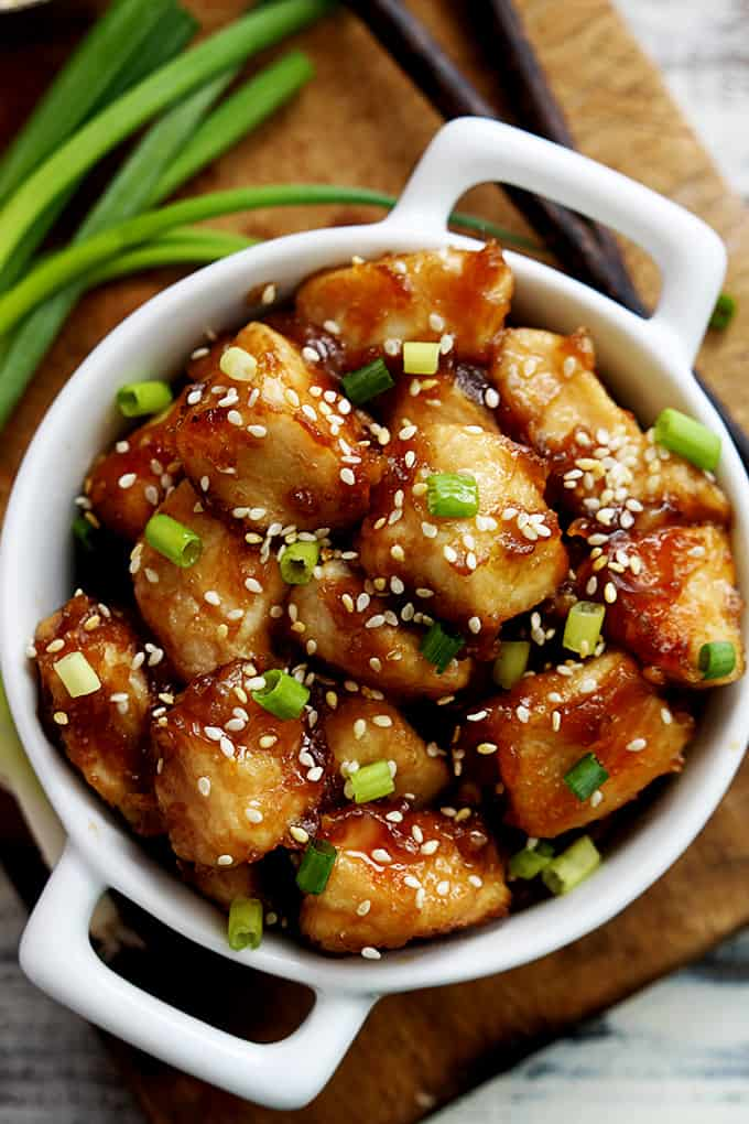 top view of baked sesame chicken in a bowl with green onions on the side.