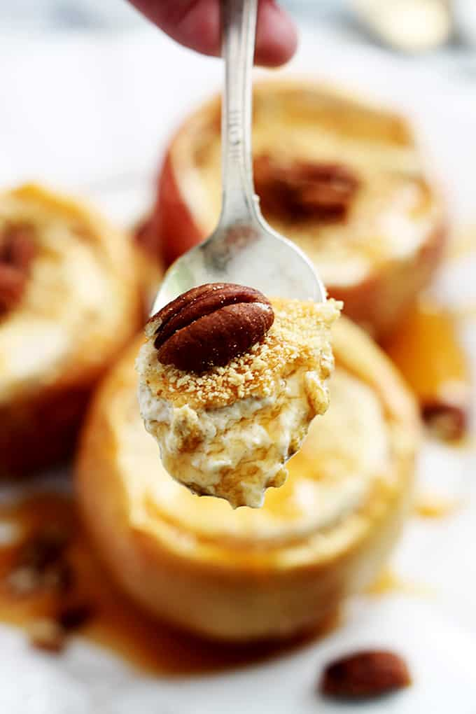 a scoop of cheesecake stuffed baked apples on a spoon with stuffed apples faded in the background.