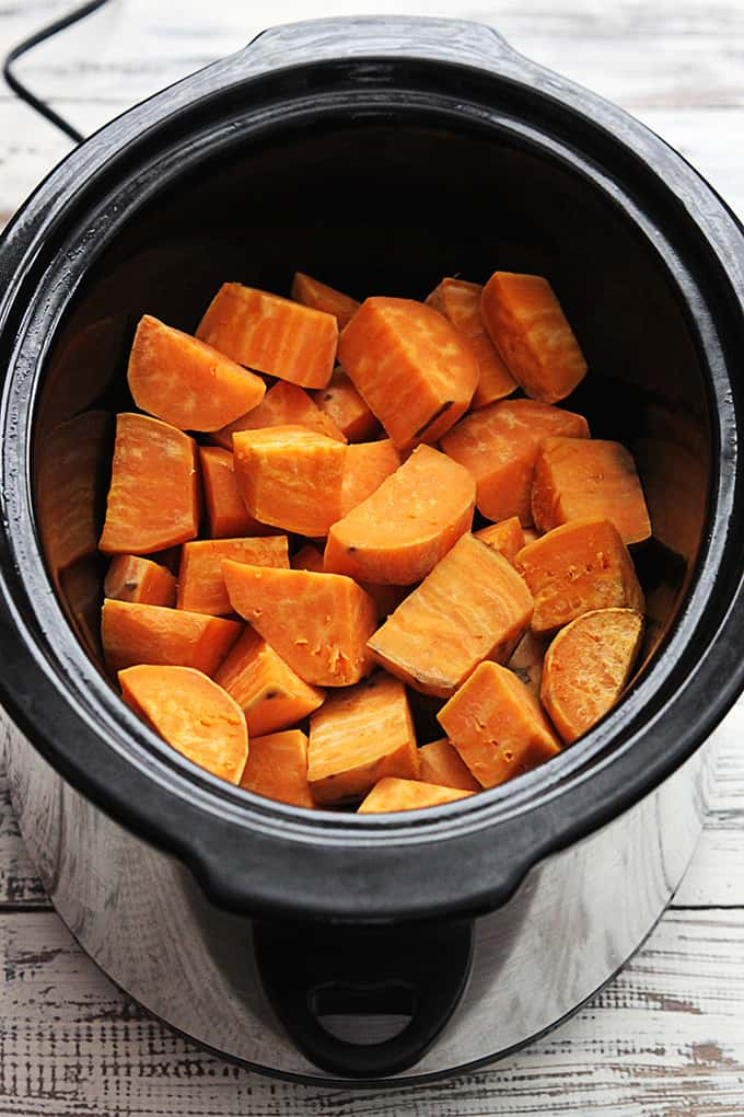 top view of cut up raw sweet potatoes in a slow cooker.