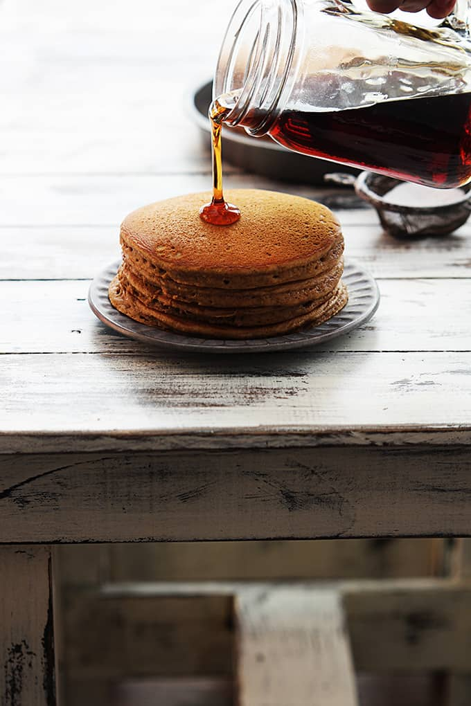 a stack of gingerbread pancakes on a plate with syrup being poured on top.