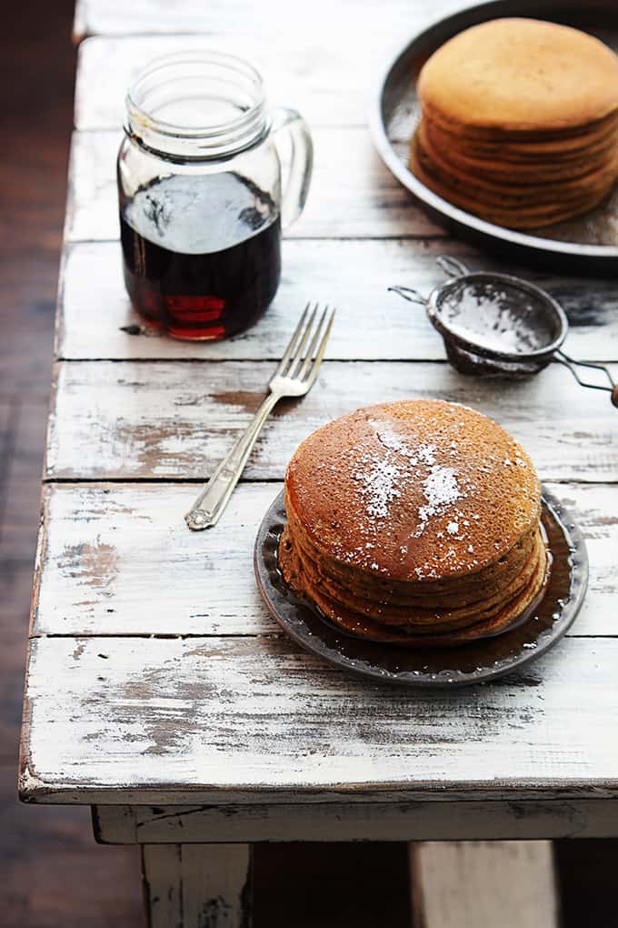 a stack of gingerbread pancakes topped with syrup and powdered sugar with a knife, sifter, a jar of syrup and more pancakes on the side.