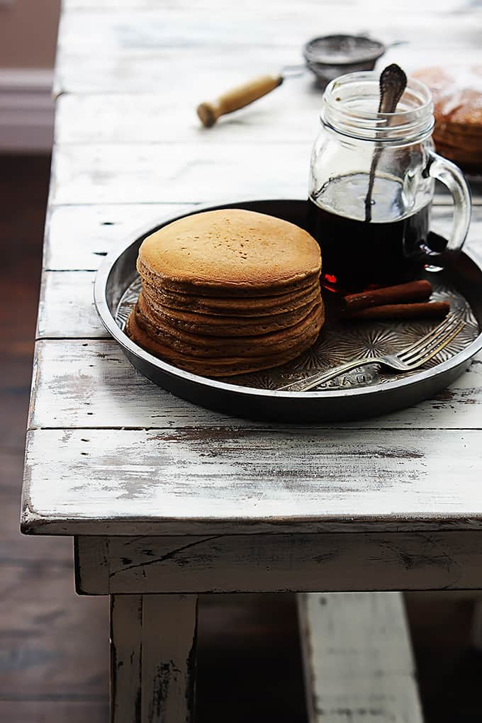 a stack of gingerbread pancakes, a knife, cinnamon sticks and a jar of syrup on a round serving tray.