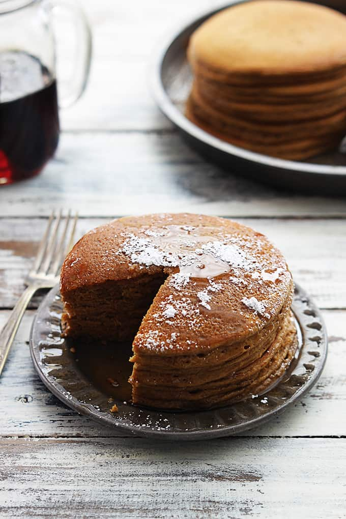 a stack of gingerbread pancakes with a bite missing with a fork, a jar of syrup and more pancakes in the background.