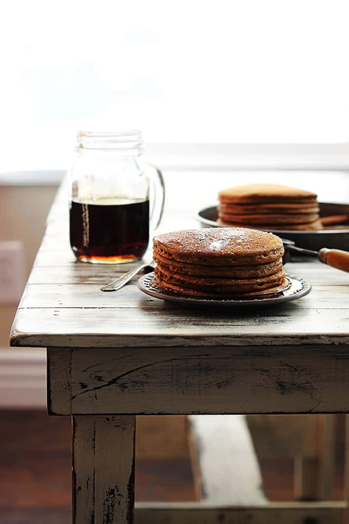 a stack of gingerbread pancakes on a plate with a mason jar of syrup on the side and more pancakes in the background all on a wooden table.