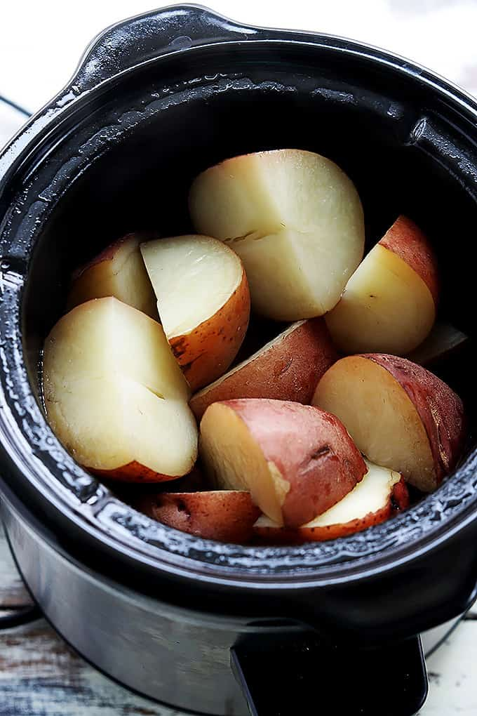 top view of raw cut up potatoes in a slow cooker.