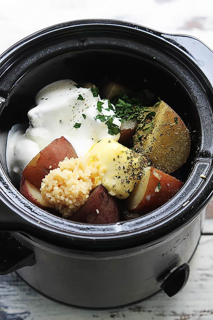 top view of a slow cooker with unmixed raw ingredients.