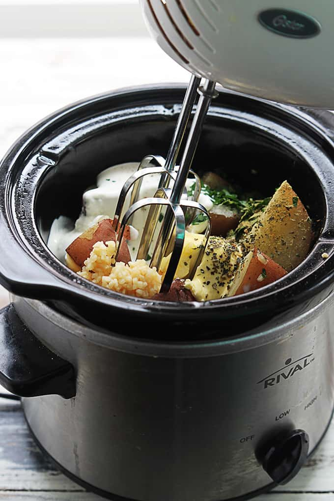 a blender being held above raw ingredients in a slow cooker.