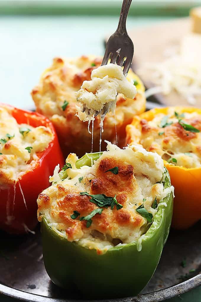 three cheese macaroni stuffed peppers with a fork with a bite of macaroni on it above the front pepper.