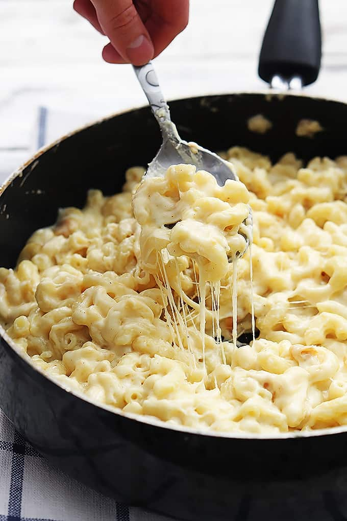 a hand scooping a spoonful of three cheese macaroni from a skillet.
