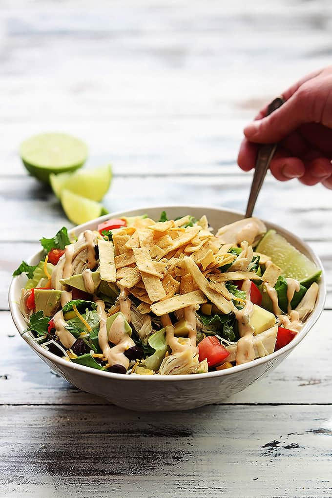 a hand holding a fork in a bowl of leftover turkey taco salad with slices of lime in the background.