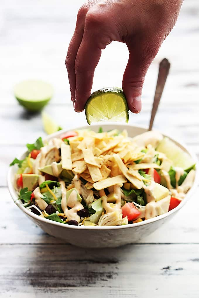 a hand squeezing a lime above a bowl of leftover turkey taco salad.