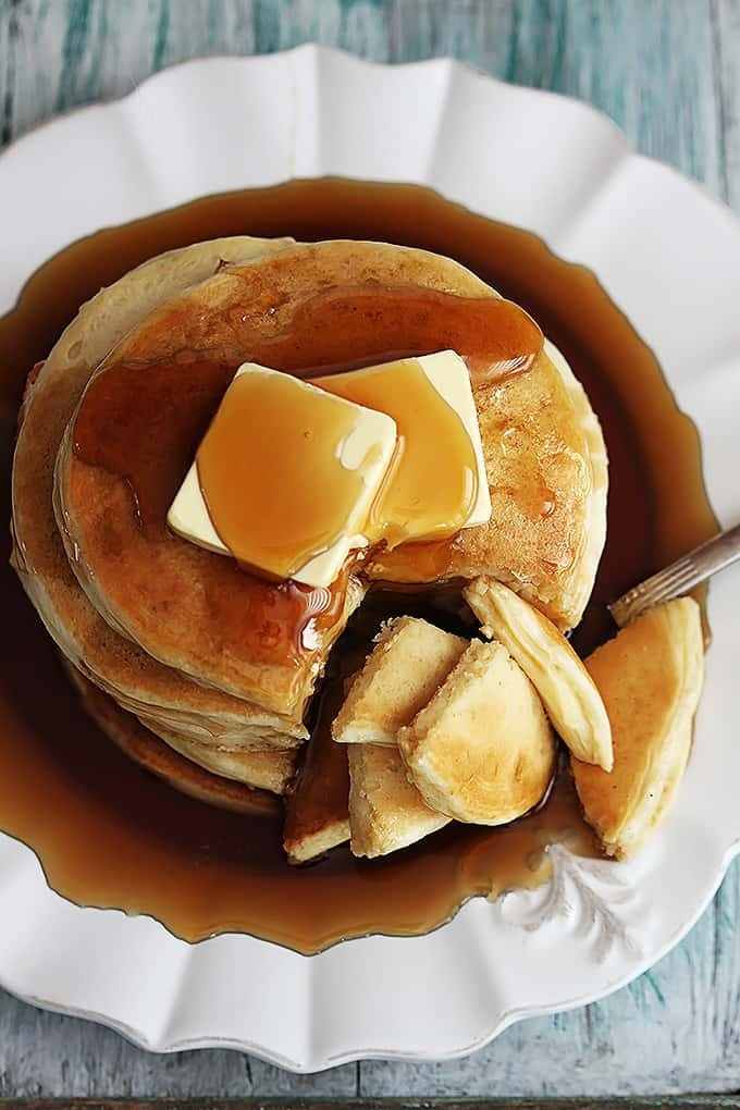 top view of a stack of greek yogurt pancakes on a plate with butter and syrup on top.