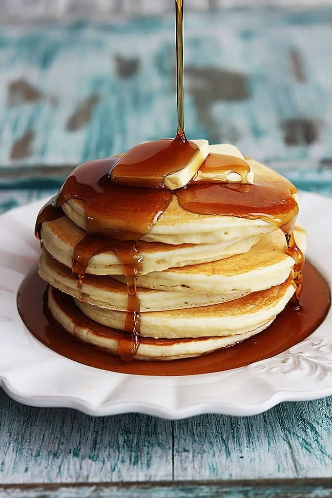 a stack of greek yogurt pancakes on a plate topped with butter with syrup being poured on top.