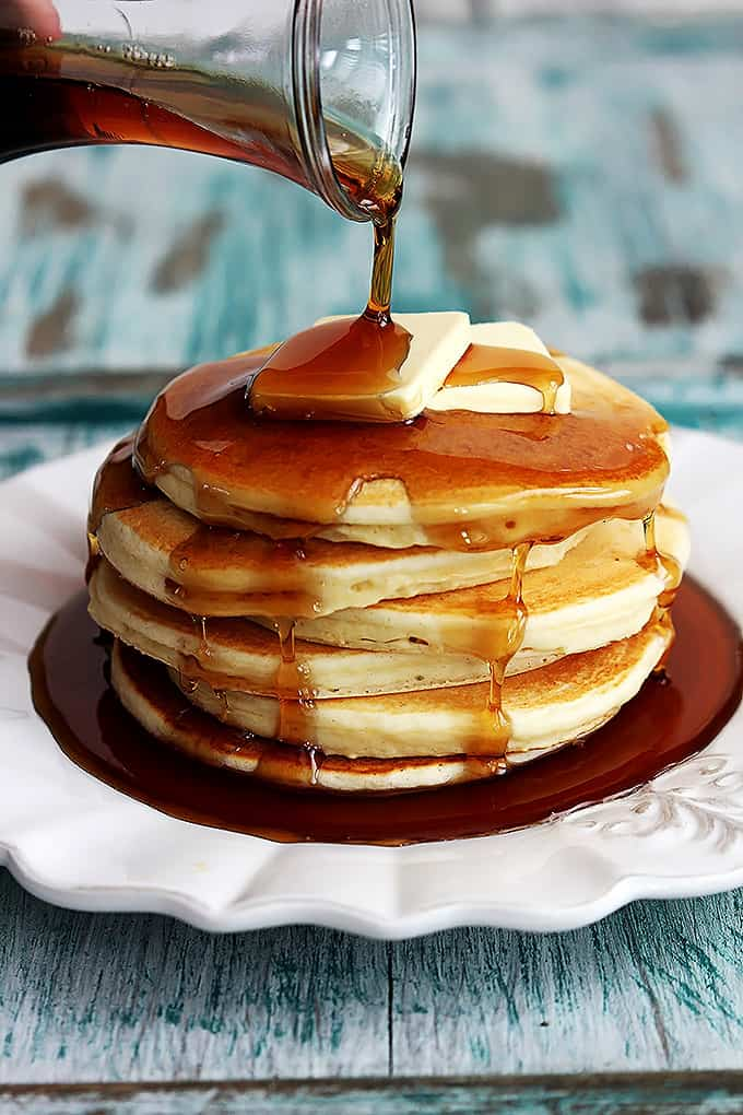 a stack of greek yogurt pancakes on a plate topped with butter and syrup being poured on top.