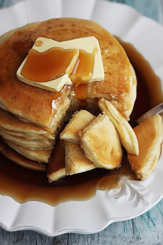 close up of a stack of greek yogurt pancakes on a plate topped with butter and syrup.