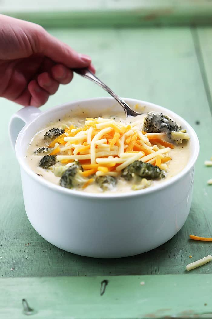 a hand scooping a spoonful of slow cooker broccoli cheese soup from a bowl.