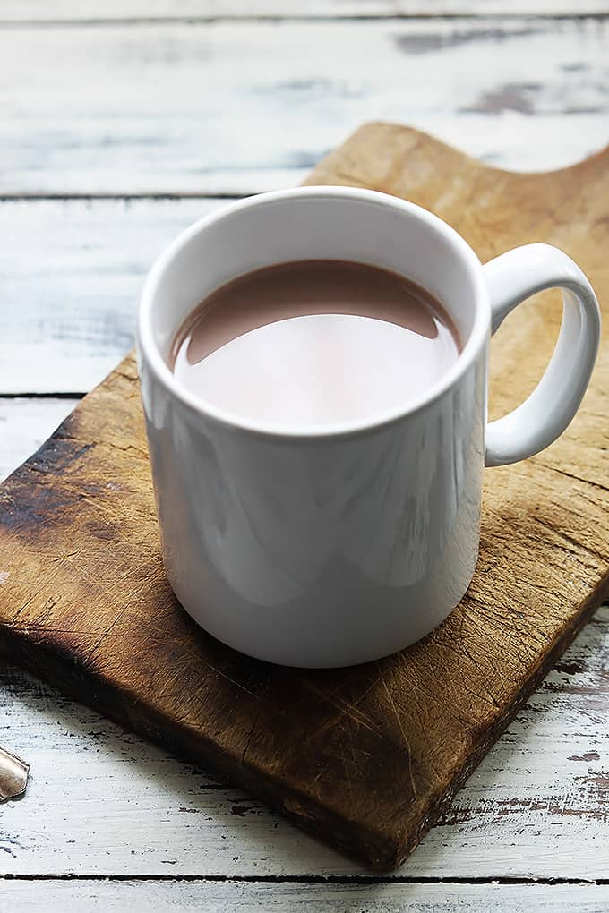 slow cooker salted caramel hot chocolate in a mug on a wooden cutting board.