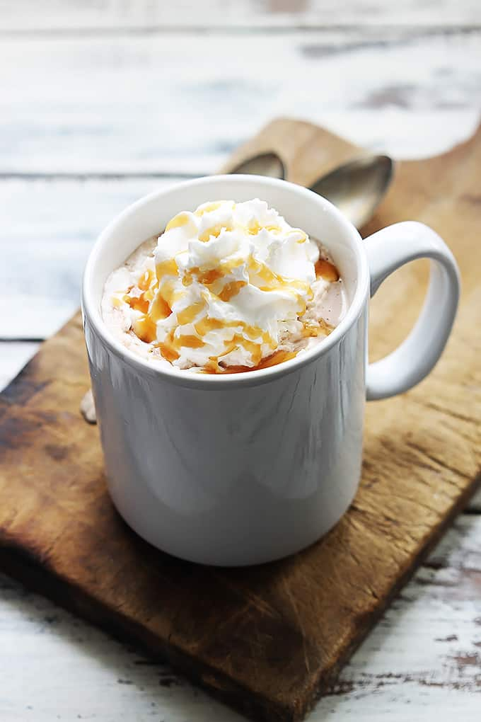 slow cooker salted caramel hot chocolate in a mug topped with whipped cream and caramel on a cutting board.