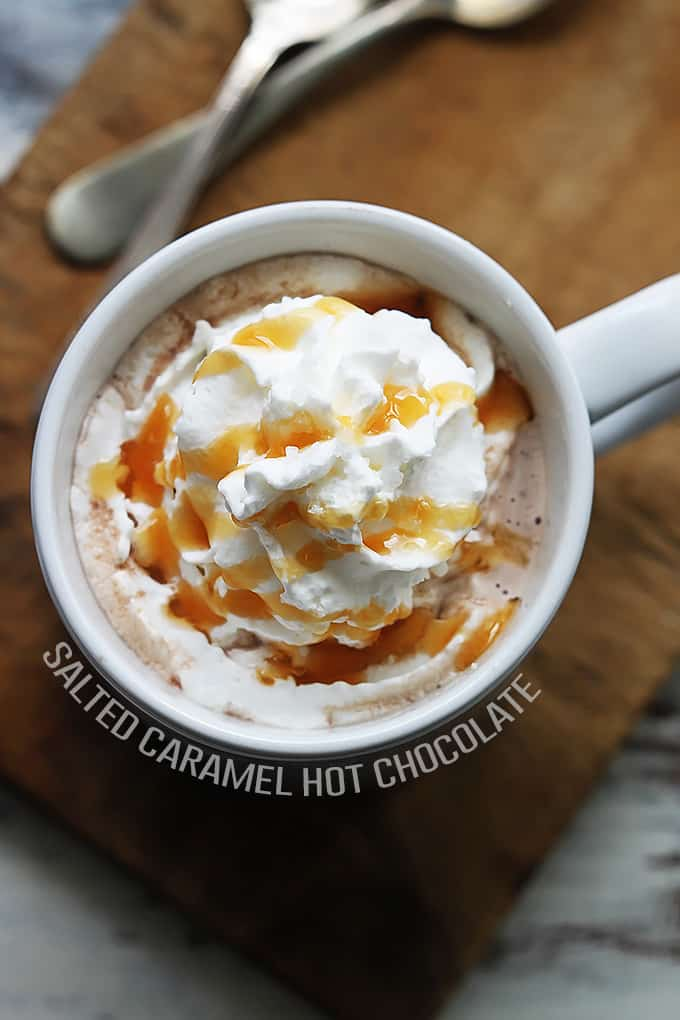 top view of slow cooker salted caramel hot chocolate in a mug topped with whipped cream and caramel with the title of the recipe written around the bottom part of the mug.