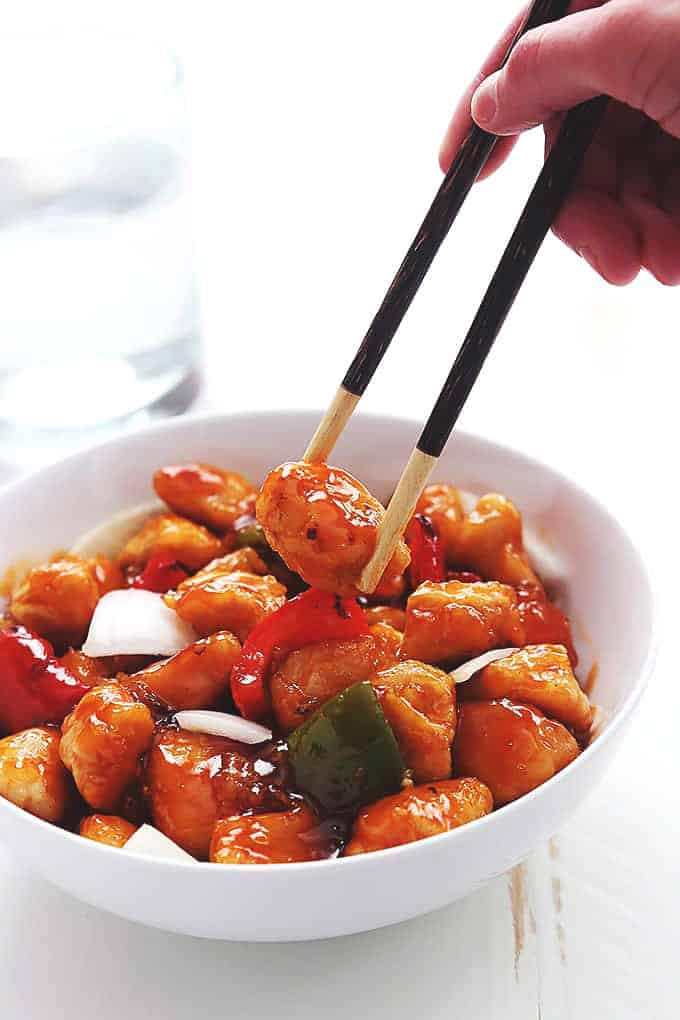 sweet and sour chicken with onions and bell peppers in a white bowl with chopsticks