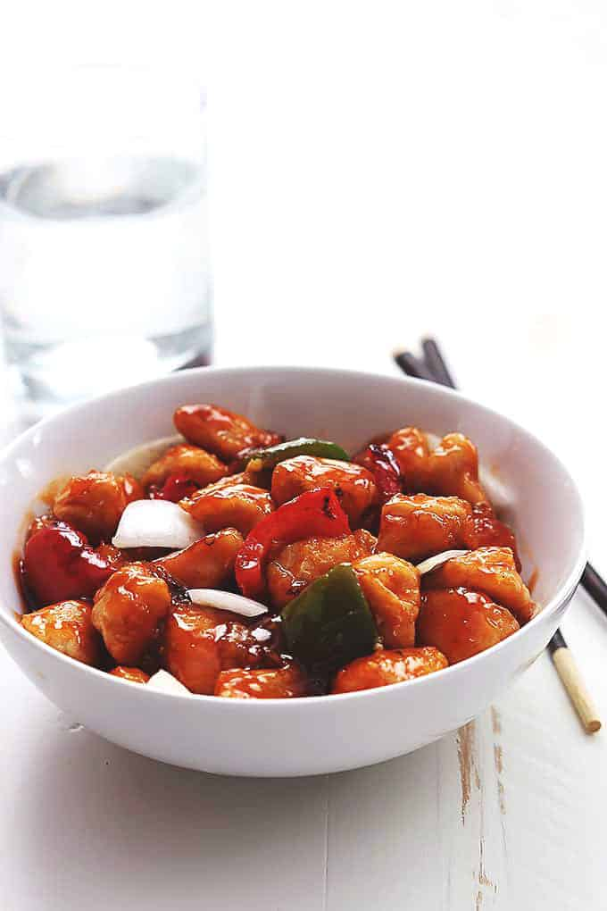 sweet and sour chicken with onions and bell peppers in a white bowl