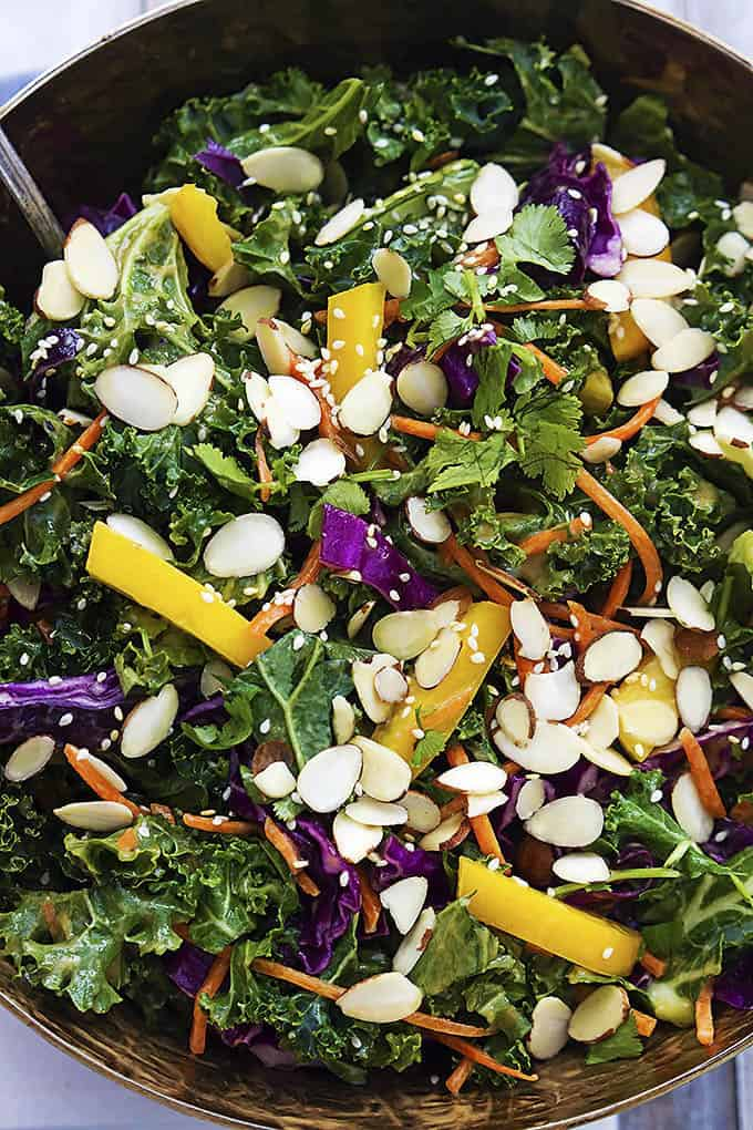 close up top view of Asian kale salad with creamy peanut dressing in a salad bowl.