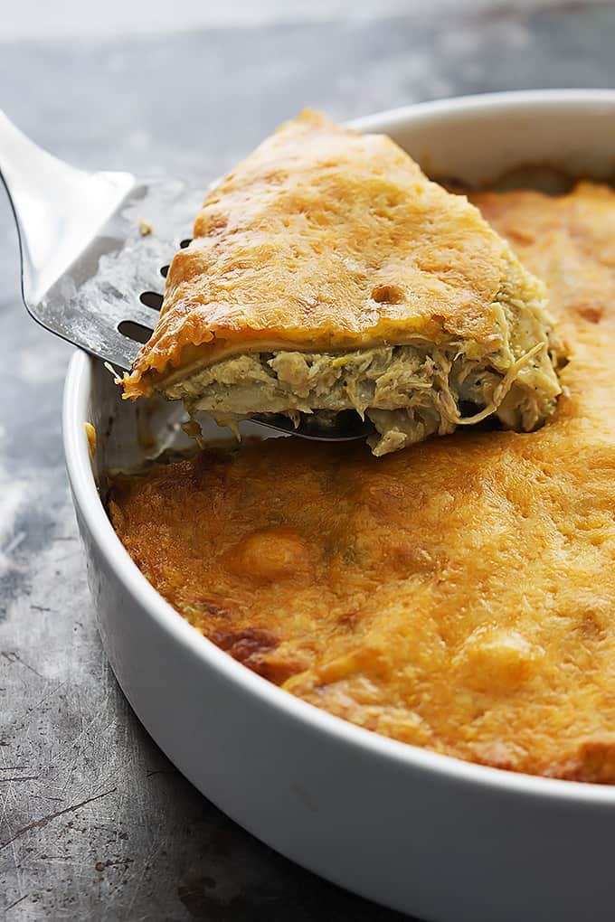 a spatula scooping some chicken verde tortilla pie out of a round serving pan.