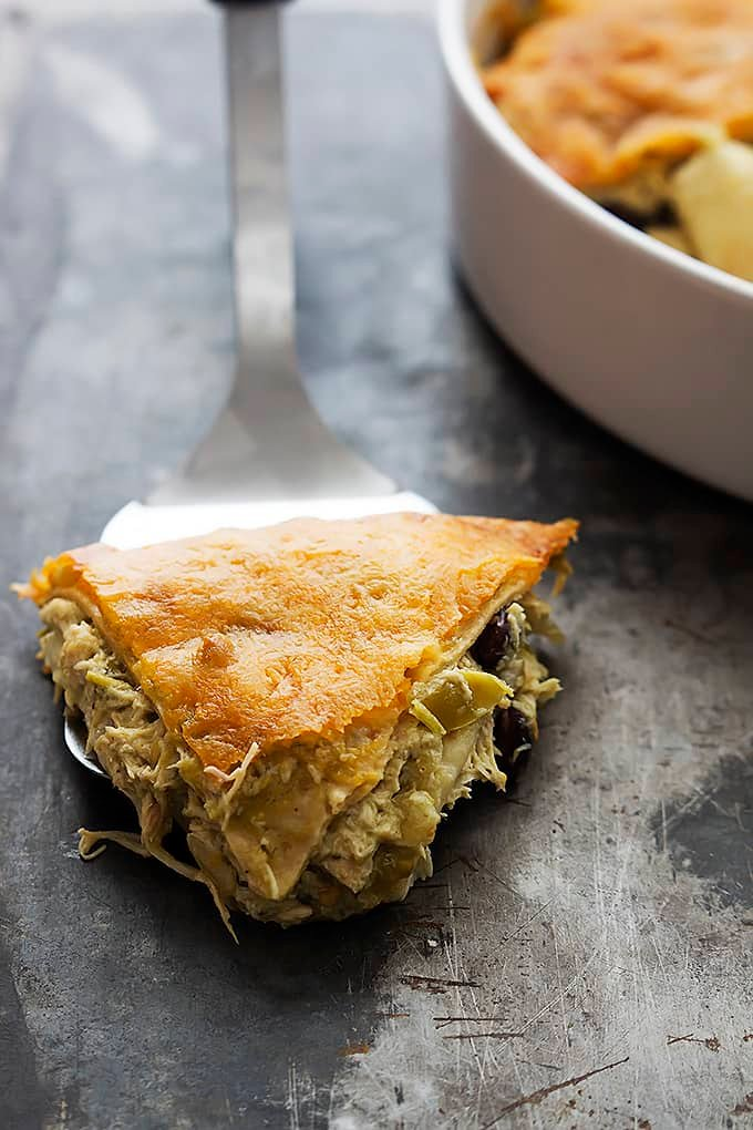 a spatula with a slice of chicken verde tortilla pie on top with the rest of the pie in a round serving pan on the side.