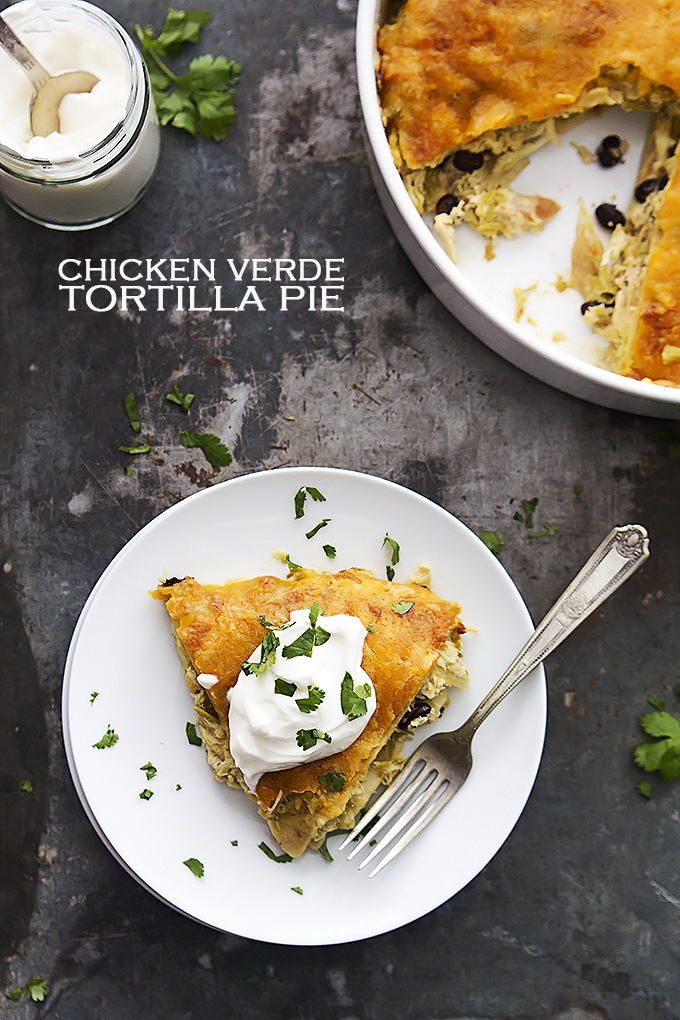 top view of chicken verde tortilla pie with a fork on a plate with a jar of sour cream and the rest of the pie in a round serving pan with the title of the recipe written on the top left side of the image.