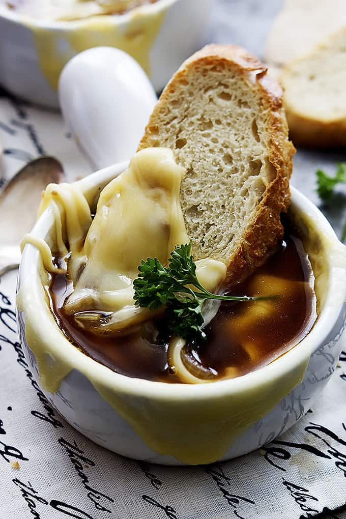 close up of a bowl of French onion soup with a slice of bread dipped inside.