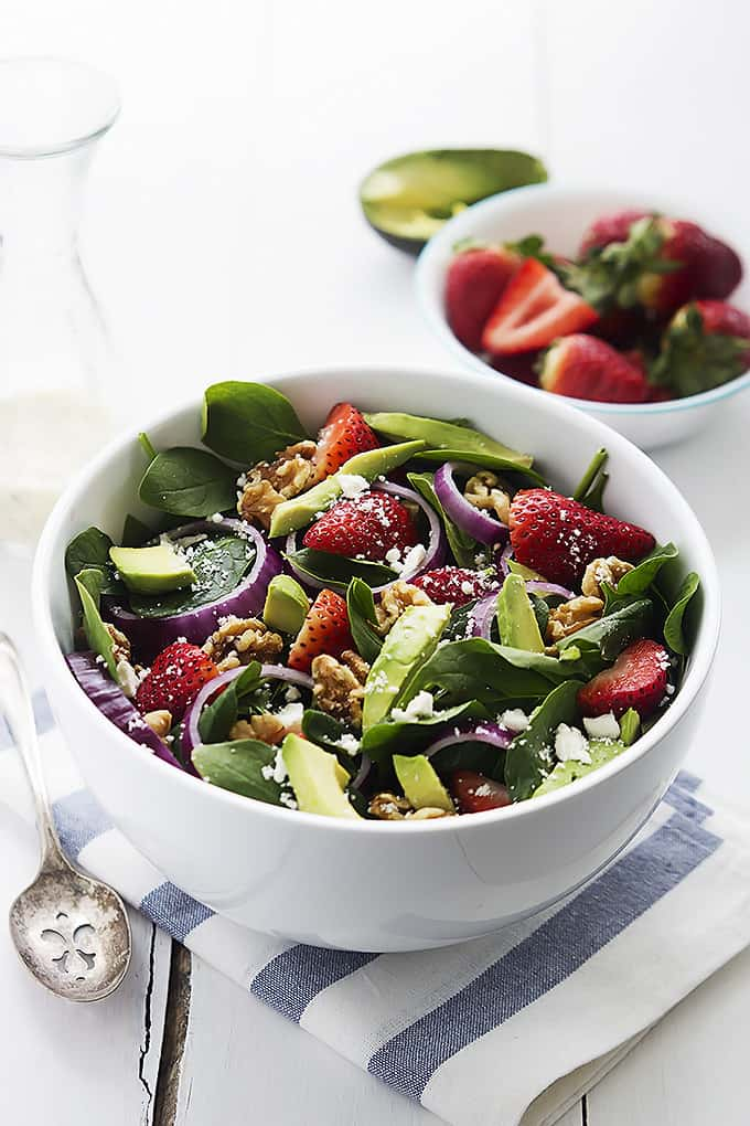 strawberry avocado spinach salad in a bowl with a bowl of strawberries in the background.
