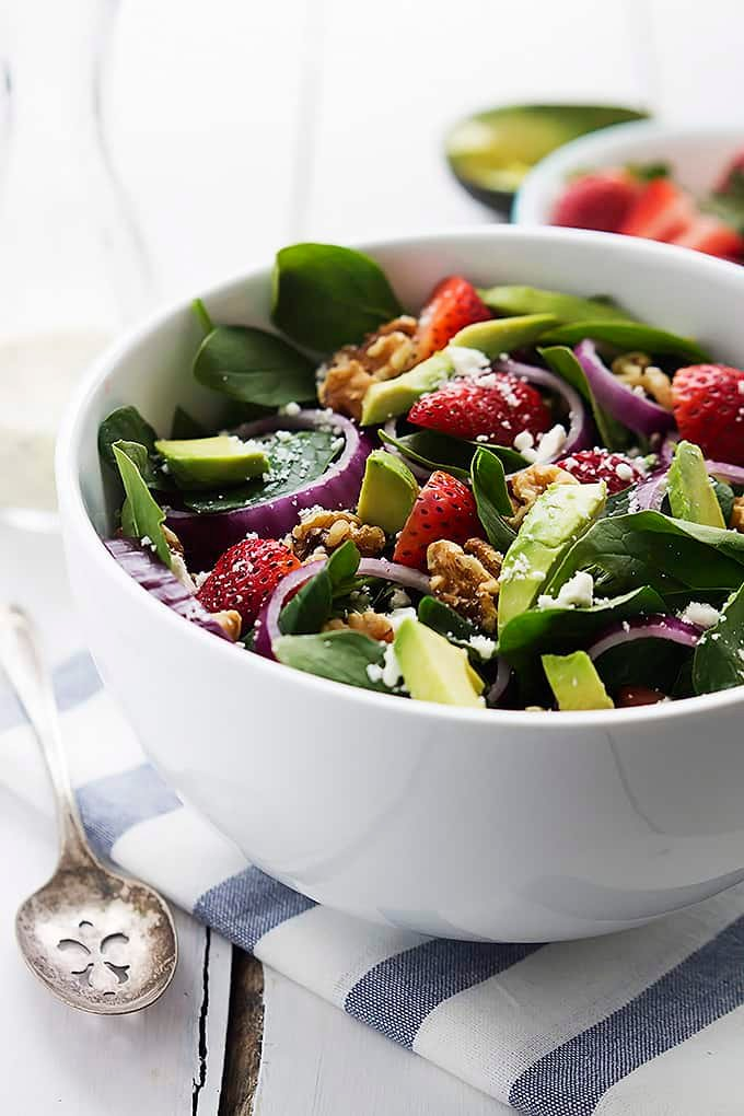 strawberry avocado spinach salad in a bowl with a spoon on the side.