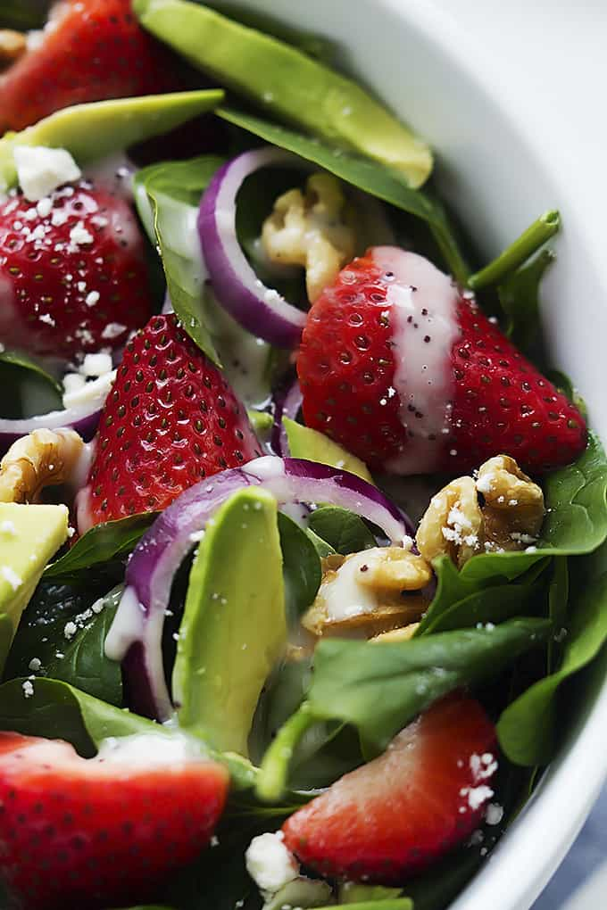 close up of strawberry avocado spinach salad in a bowl.