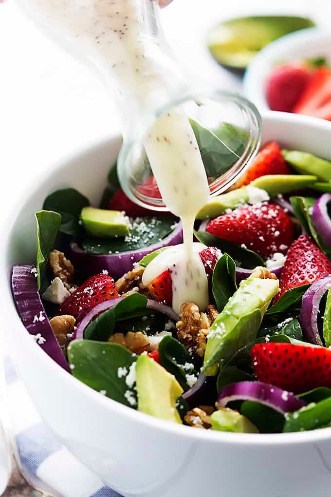 close up of dressing being poured on top of strawberry avocado spinach salad in a bowl.