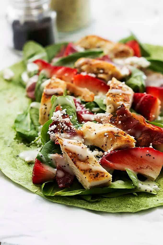close up of a open strawberry chicken bacon & spinach wrap with poppyseed dressing.