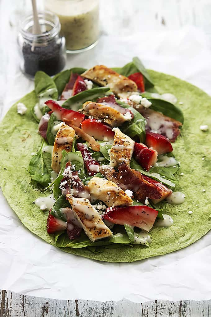 a strawberry chicken bacon & spinach wrap with poppyseed dressing open on a table with a jar of dressing and a jar of poppyseeds on the side.