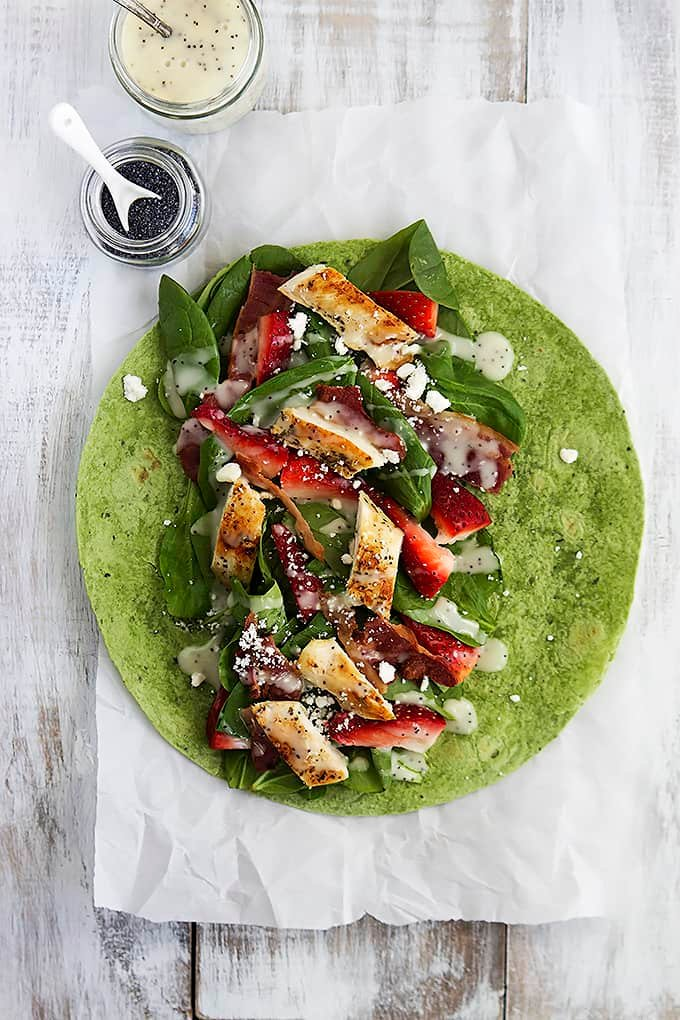 top view of a strawberry chicken bacon & spinach wrap with poppyseed dressing open on a table with a jar of dressing and a jar of poppyseeds on the side.