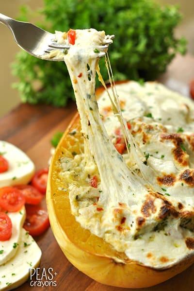 a fork lifting a bite of pesto chicken lasagna stuffed squash from a squash.