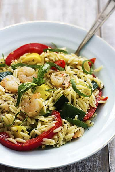 shrimp & veggie orzo with pesto vinaigrette with a fork in a bowl.