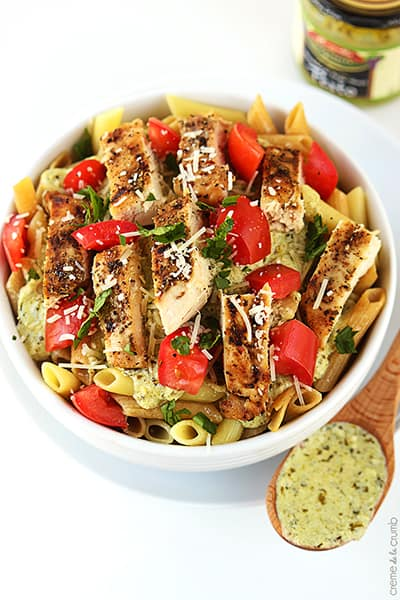 top view of creamy pesto chicken penne pasta in a bowl with a wooden serving spoon on the side with pesto on top.