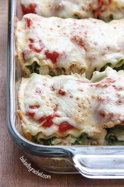 close up of pesto chicken lasagna rolls in a serving tray.