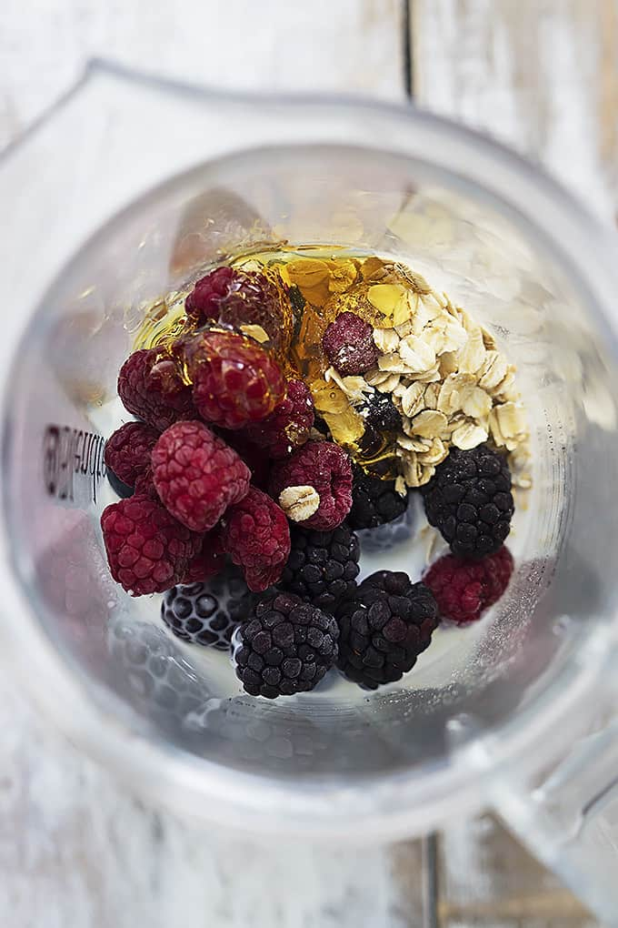 top view of berry oat breakfast smoothie ingredients unmixed in a blender.